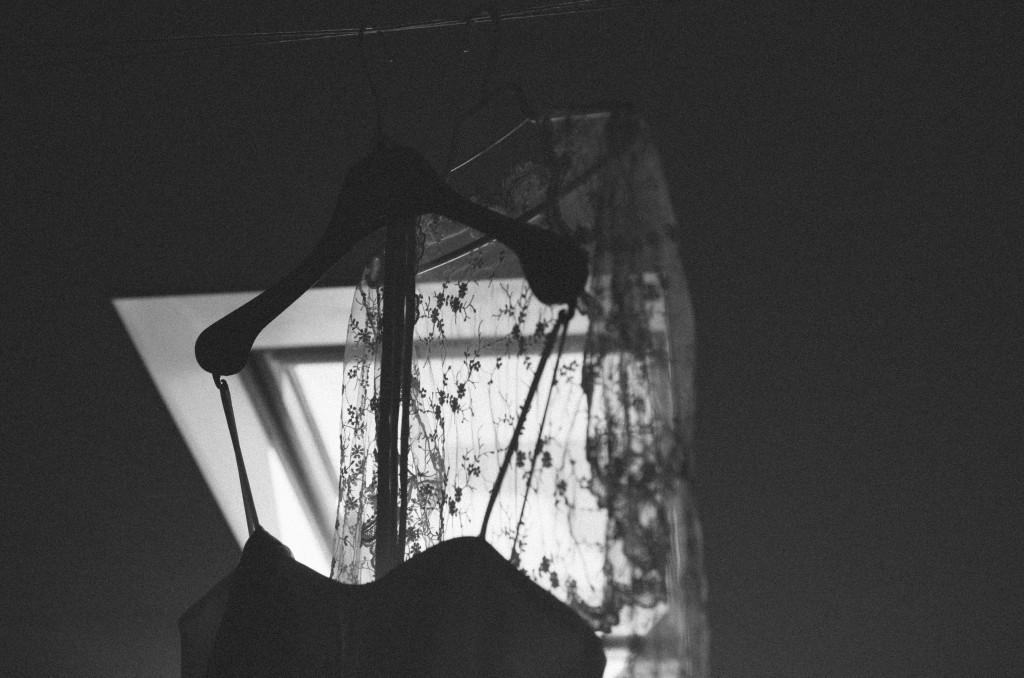 Hochzeitskleid hängt vor Fenster