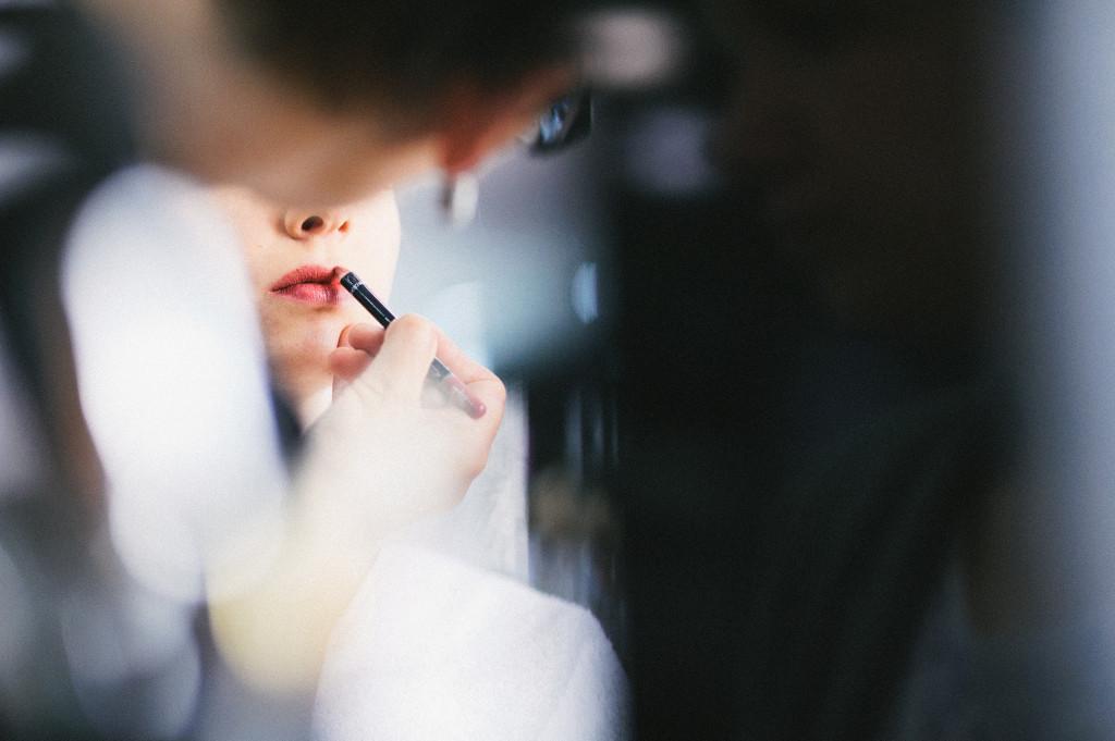 Kosmetikerin trägt Braut Lippenstift auf