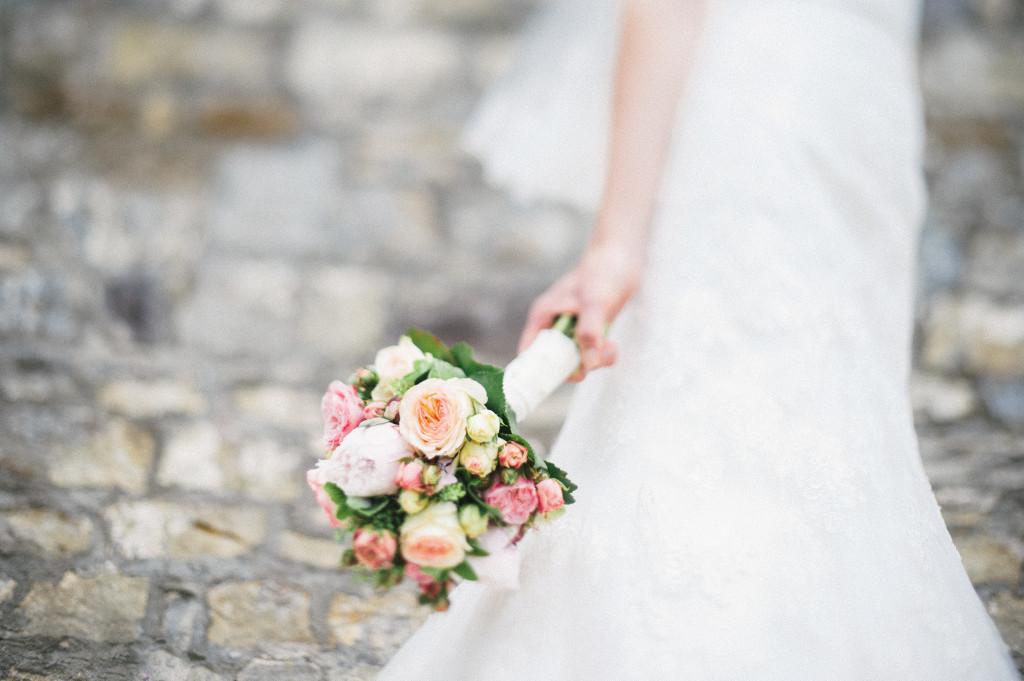 54_Hochzeitsreportage_Wuerzburg_Portrait_Brautstrauss_Residenz_Steinwand_Freelensing