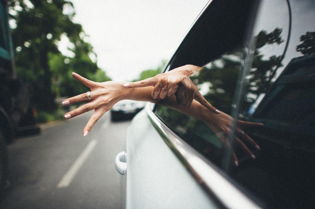 Braut hält Hand mit Ehering aus dem Fenster des Autos