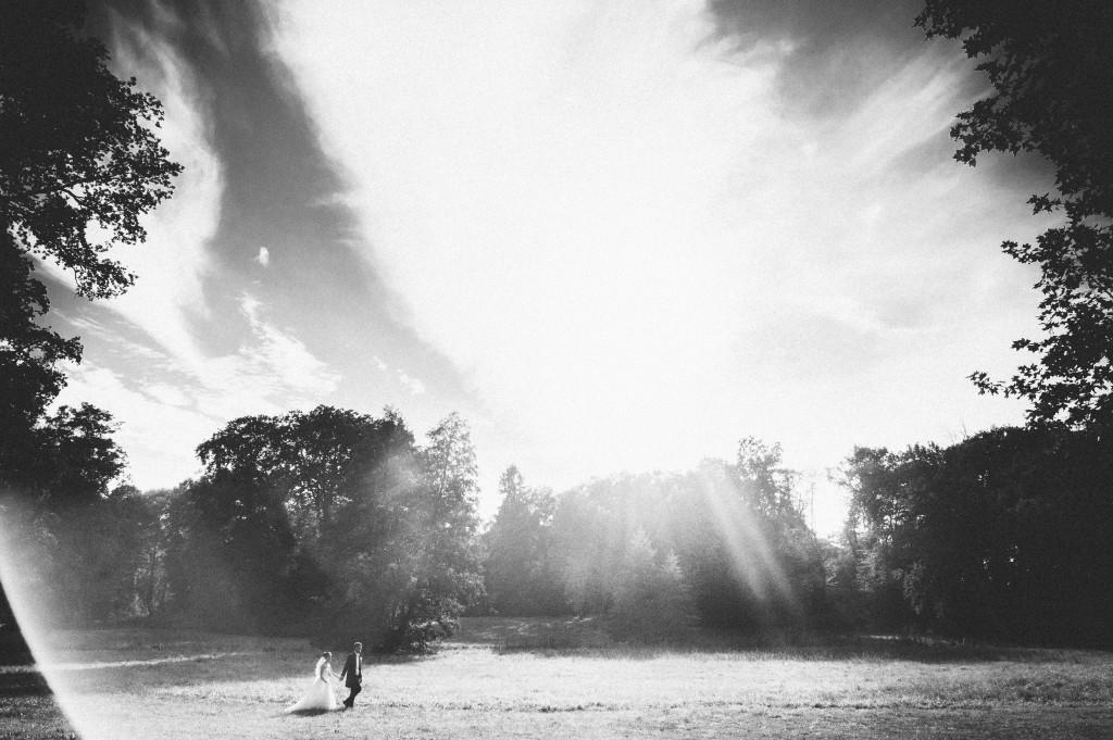 Brautpaar läuft über eine Wiese im Gegenlicht