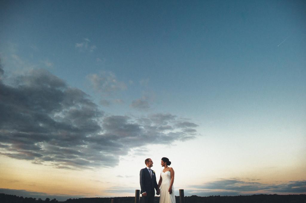Brautpaar auf einem Steg bei Sonnenutergang